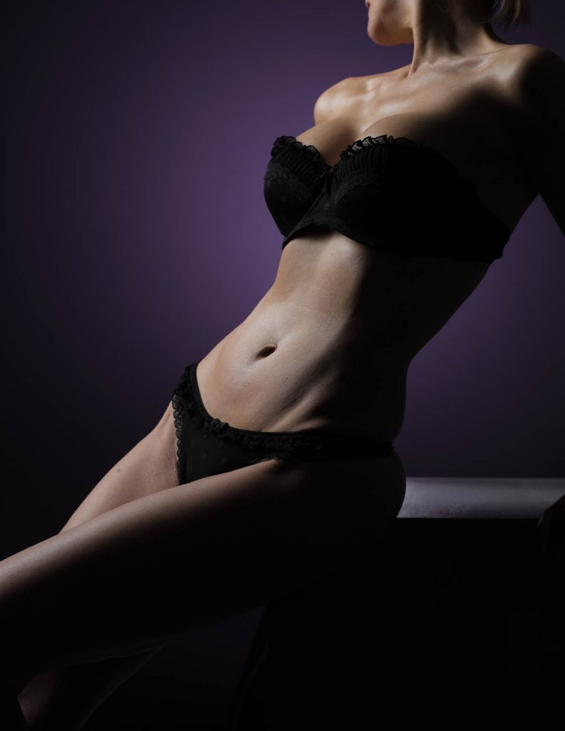 Akt-Fotoshooting des Körpers einer sitzenden Frau in schwarzer Unterwäsche und trägerlosem BH