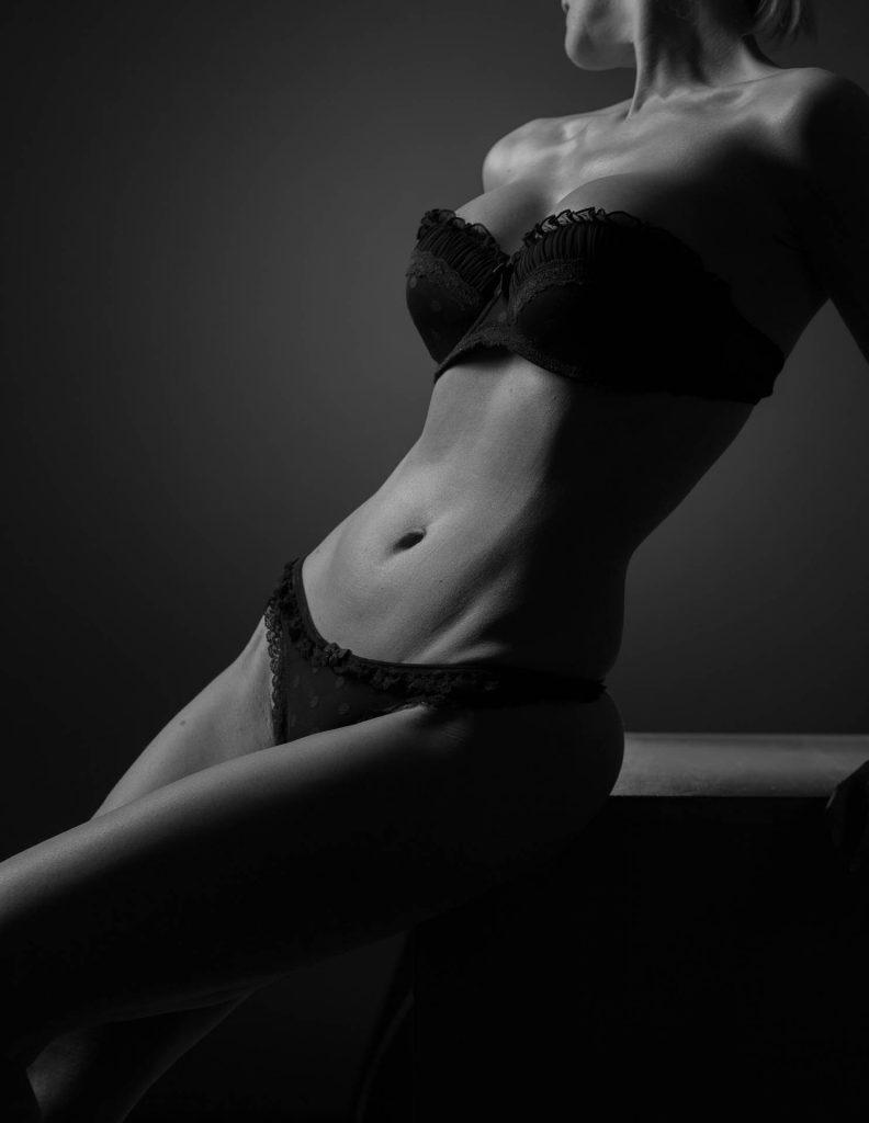 Erotikfoto des Körpers einer sitzenden Frau in schwarzer Unterwäsche und trägerlosem BH