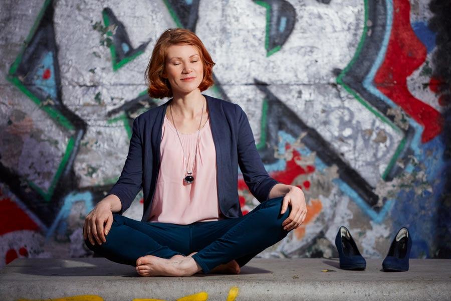 Business-Portrait der Burn-Out Coachin Suzy Roß meditiert barfuß vor einer Mauer mit buntem Graffiti