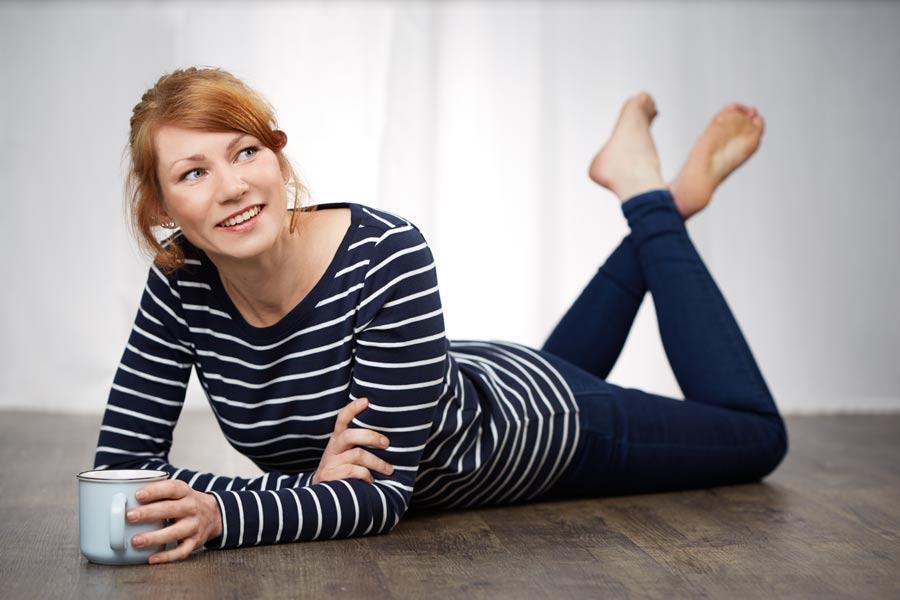 Business-Portrait der Burn-Out Coachin Suzy Roß, die mit einer Tasse Tee entspannt auf dem Boden liegt.