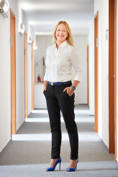 Businessportraits von Sandra Lenzenhuber, Geschäftsführerin des BVI Bundesfachverbandes der Immobilienverwalter. Sie steht im Flur der Büros.